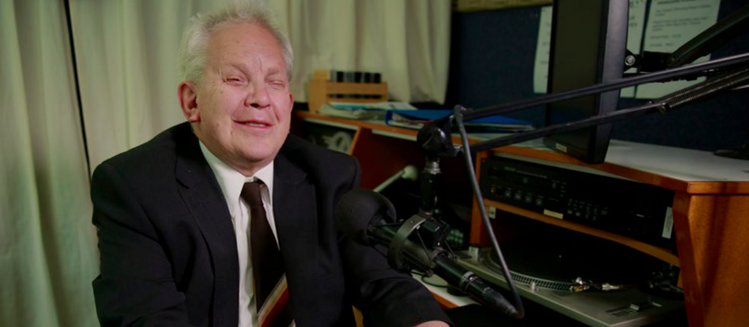 Vision impaired man in studio in front of microphone, operating a community radio console.