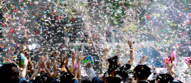 Crowd throwing coloured confetti in the air to celebrate