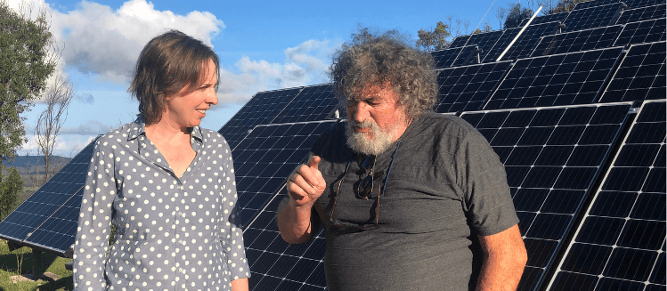 Jo Curtin and Roger Wood standing in front of new solar panels
