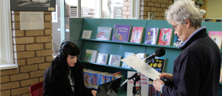 Two women in library. One wears headphones and looks at computer. Another stands in front of a microphone reading and speaking.