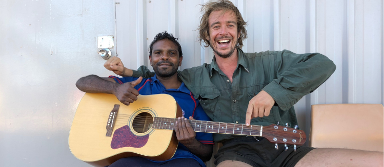 Archer and Wilcannia local Eric holding a guitar
