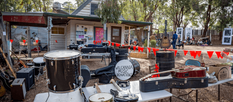 Wilcannia River instrument donation concert at Lot 19 with instruments displayed on table in the foreground