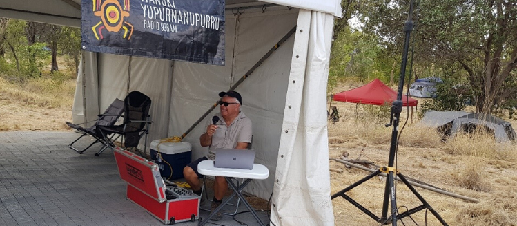 Seated older man, Wayne Bynder, with a cap and microphone broadcasting in a tent in the bush south east of Fitzroy Crossing