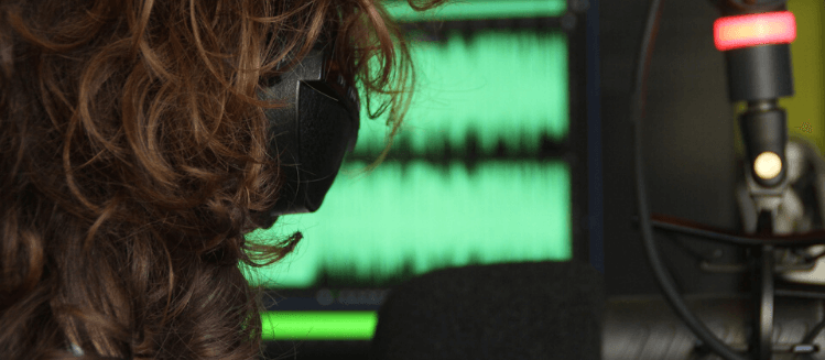 Back of a female announcer's head looking at screen with headphones