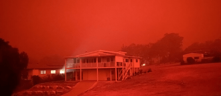A two story house lit by a burnt red bushfire sky at Mallacoota in December 2019