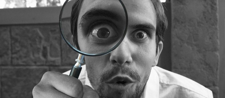 Black and white photo of man with a beard holding a magnifying glass up to his right eye