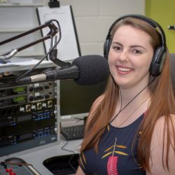 colour photo of smiling woman in radio studio