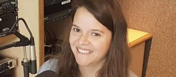 Hannah Rogers smiling in front of a stufio microphone