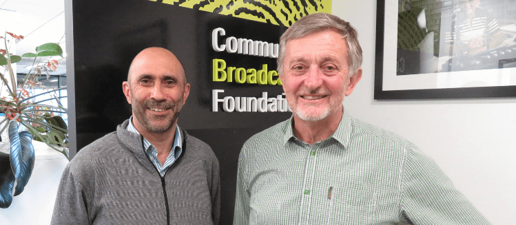 Two men standing in front of Community Broadcasting Foundation logo