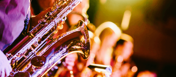 Close up of saxophone being played in a band (other band members blurred in background)