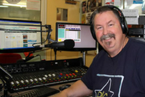 Jeffrey Cullen - community broadcaster at Plenty Valley FM, in studio smiling at camera