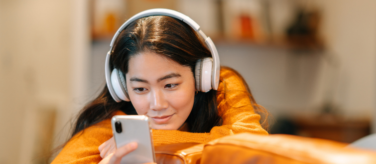 Young woman with headphones looking at her phone