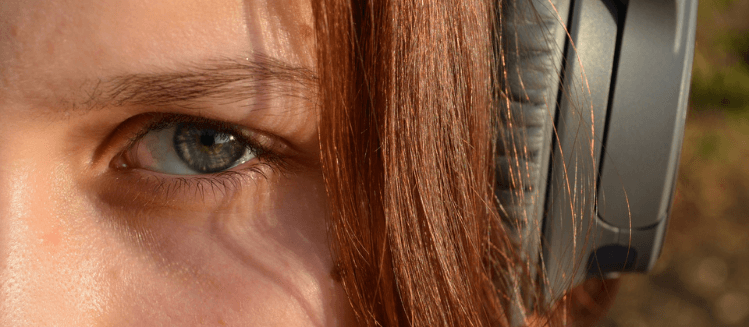 Close up of an auburn-haired woman's left eye with black headphones