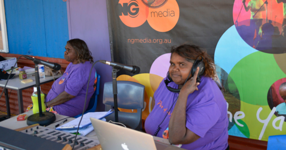 Indigenous community broadcaster for NG Media, sitting in front of a Mac laptop and another broadcaster.