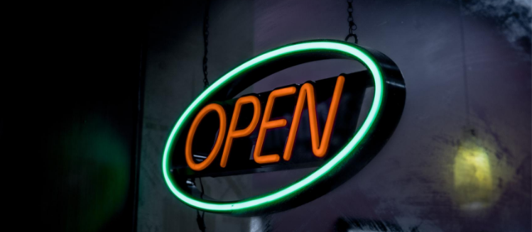 Large green and red neon sign that says 'Open'
