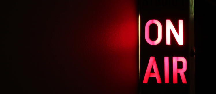 On-air illuminated red sign on a dark wall