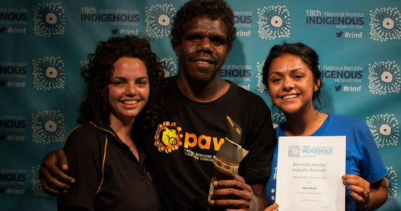 Three Indigenous broadcasters against background printed with 18th National Remote Indigenous Media Festival. Holding a certificate and an award.