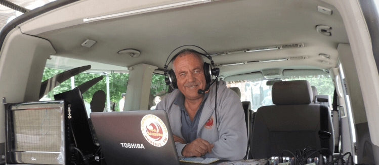 Smiling man with headphones in outside broadcast van