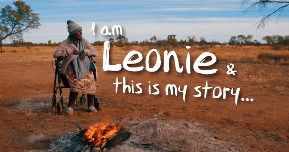An Indigenous woman sitting around a campfire surrounded by the red earth of the Australian outback