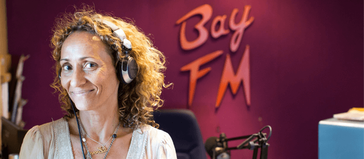 Women in studio wearting headphones. Bay FM logo in background