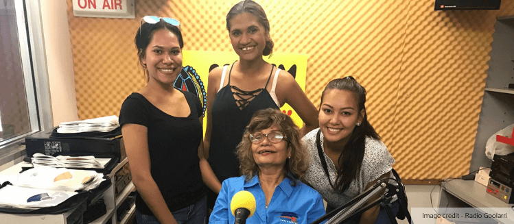 Community broadcaster Sandra Dan in studio with three female guests. Gathered around microphone, smiling at camera