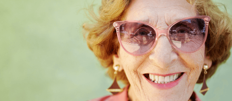 Older woman smiling at camera wearing pink sunglasses