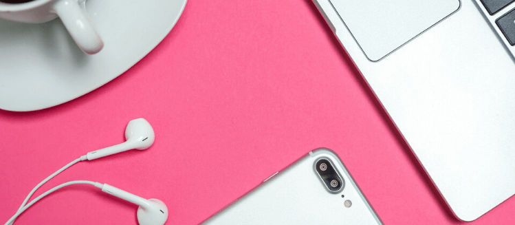Computer, phone and cup of tea on bright pink background