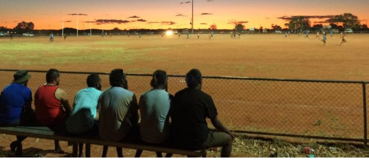 A row of men sitting on bench at sunset watching a football game in Yuendumu