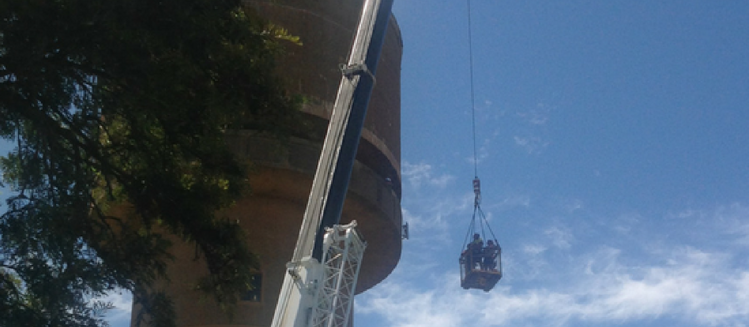 Crane lifting an installation crew to install a new antenna