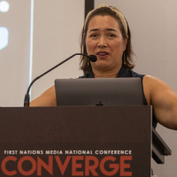 Catherine Liddle standing behind the podium at the converge conference giving a presentation