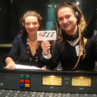 A woman and man wearing headphones in the Radio 3ZZZ studio holding a small ZZZ signstudios
