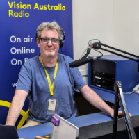 Vision Australia presenter with headphone in the studio behind a microphone