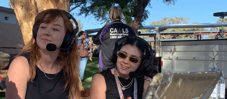 Two female presenters from 8CCC wearing headsets at an outdoor broadcast