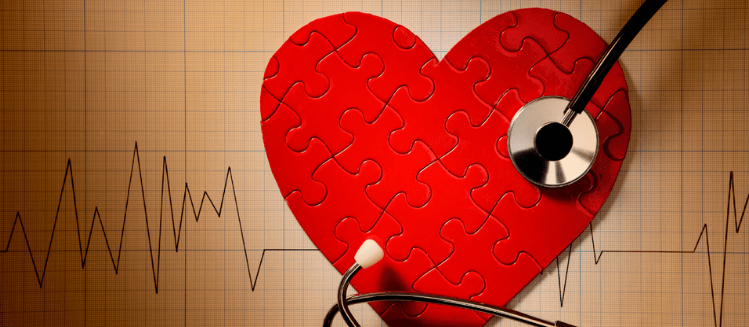 Red heart shape puzzle overlaying heart monitor print out. Stethoscope on top