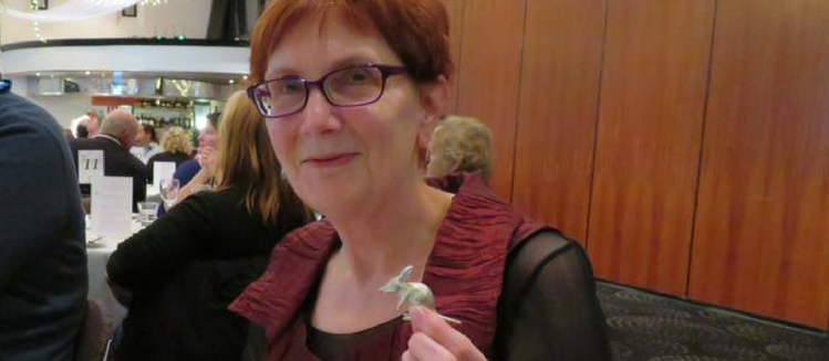 Barbara Baxter from the CBF Grants Support Team at the 2018 SACBA Awards. Holding a small silver bilby ornament and smiling at the camera