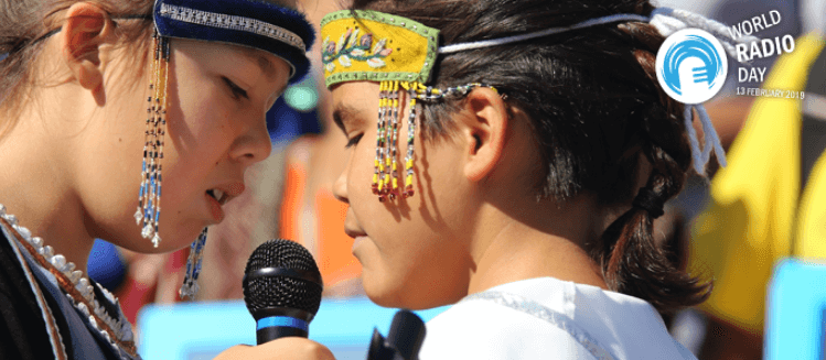 Two young girls in traditional costume talking into microphone. World Radio Day 2019
